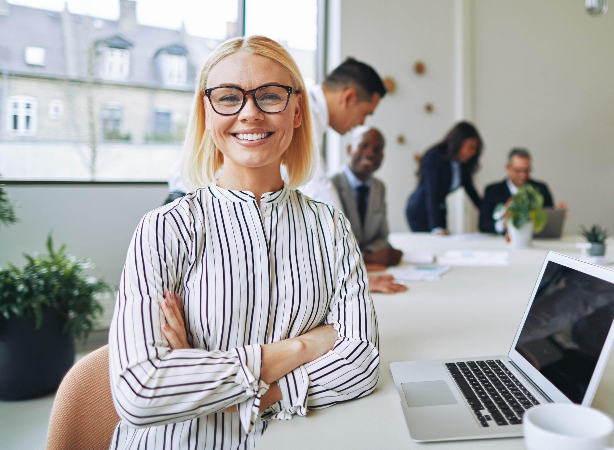 Senhora num escritório a sorrir e olhar diretamente para a câmara com colegas a falarem no fundo